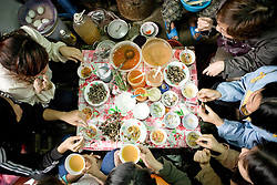 Top view of a vietnamese women's group enjoying boiled snail (op) in a street food stall. Hanoi, Vietnam, Asia.