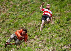 © Licensed to London News Pictures. 25/05/2015. Brockworth, Gloucestershire, UK.  The annual traditional Cheese Rolling races, which by custom take place on Bank Holiday Monday.  Participants race down the very steep Coopers Hill chasing a Double Gloucester Cheese, and injuries sometimes happen. Photo credit : Simon Chapman/LNP