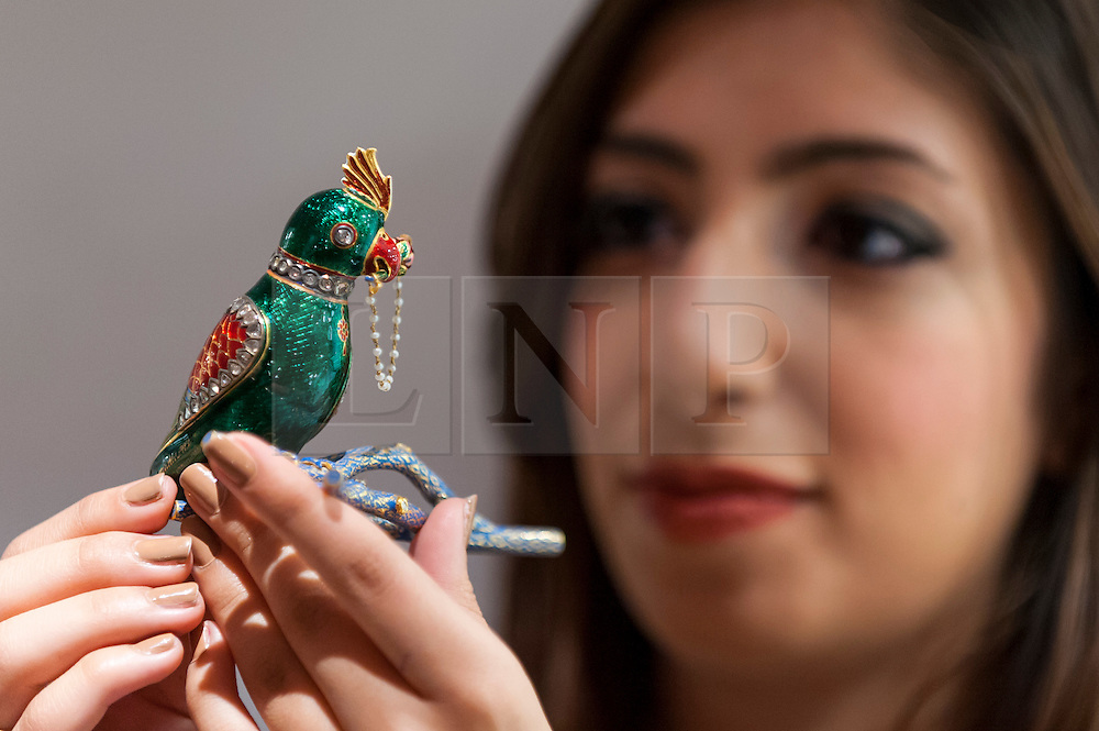 © Licensed to London News Pictures. 13/10/2016. London, UK. A Sotheby's staff member shows a gold, polychrome enamelled and gem-set parrot-from flask (chusk) on a branch, North India, 19th century (est. GBP 12-15k) at the preview of Sotheby's Art of the Middle East and India exhibition, which presents artworks to be sold in New Bond Street in four sales in October. Photo credit : Stephen Chung/LNP