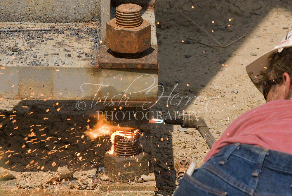 A male metalworker cuts through a bolt with a torch.