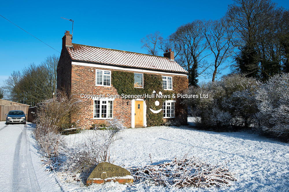 A smiley face embedded in the ivy of a snow covered cottage in the village of Hayton, East Yorkshire.