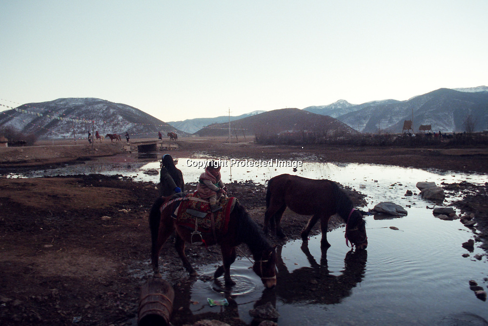 "ZHONGDIAN COUNTY, DECEMBER 19, 2000: Tibetan Kampa nomads water their horses at the end of a day, Yunnan province , December 19, 2000..Zhongdian county is believed to be part of the areas on which James Hilton's famous novel "" lost Horizon""- a description of Shangri-La- is modelled.. ."