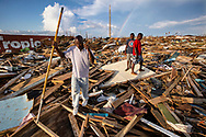 Survivors walk among the remains of homes destroyed by the wind and storm surge caused by Hurricane Dorian in an area called 'The Mudd' on Thursday, September 5, 2019 at Marsh Harbour in Great Abaco Island, Bahamas