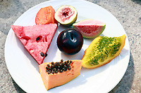 details close up of plate of exotic brazilian fruits compose of watermelon papaya plum,guava kaki and fig