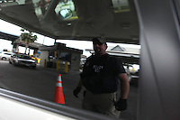 Members of ICE, Immigration and Customs Enforcement, check vehicles as they prepare to cross a bridge from Brownsville, TX to Matamoros, Mexico on April 22, 2010.  The US government has stepped up inspections of vehicles crossing over to Mexico in an attempt to try to slow the flow of drug proceeds into Mexico. (Photo/Scott Dalton)