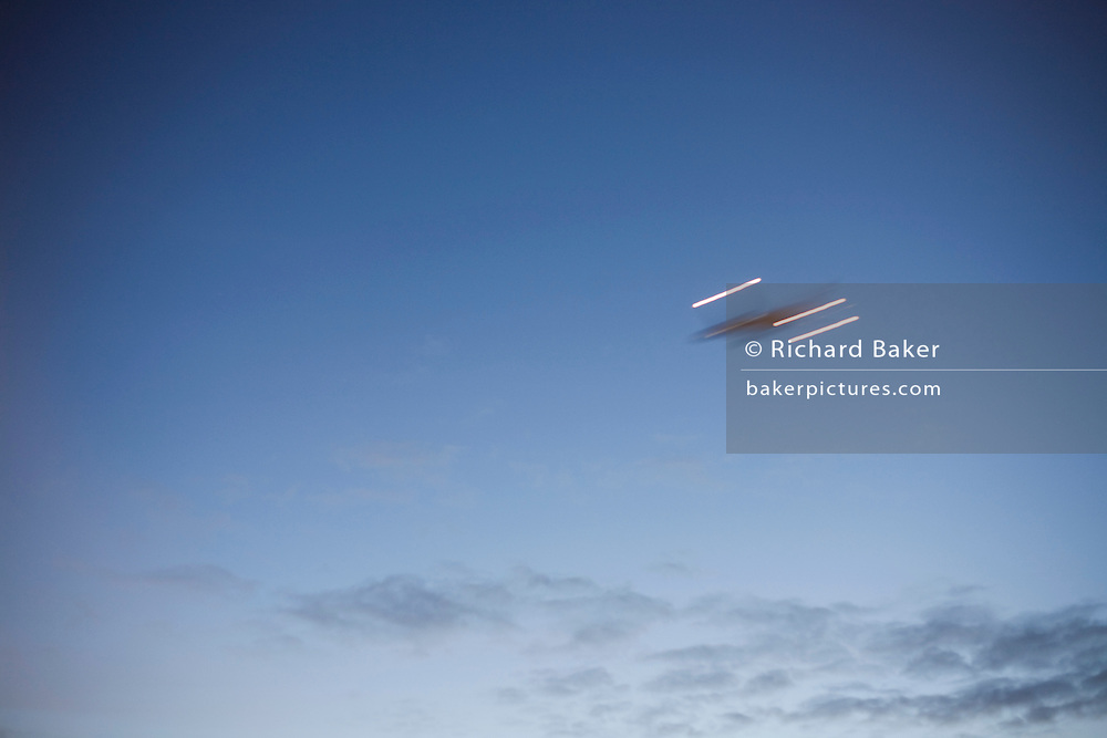 A blurred jet airliner climbs away after taking-off in clear skies above London's Heathrow Airport.