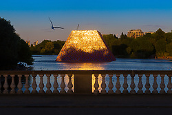 Artist Christo's 'Mastaba', an installation made up of over 7,000 barrels floating on The Serpentine in London's Hyde Park catches the setting sun and reflects it on the water. London, July 02 2018.