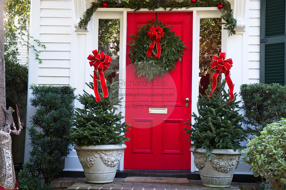A historic home decorated with a Christmas wreath and ribbons on Church Street in Charleston, SC.