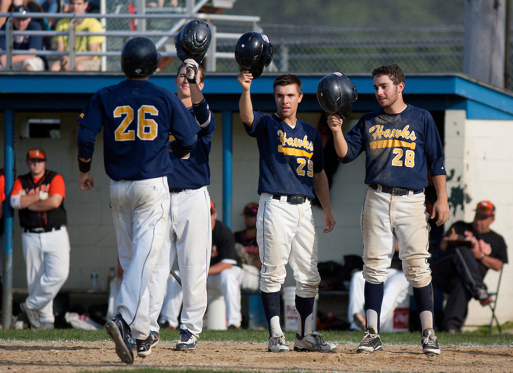 Braintree, MA 06/11/2012.Xaverian's Alex Person is welcomed at home plate by teammates Tim Duggan, left, Chris Hoyt, center, and Nick Ahearn, right, after his home run in the 8th inning of Monday's MIAA Division 1 South Finals at Braintree High School..Wicked Local Photo by Alex Jones