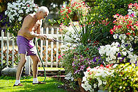 Jerry Sorbel, 80, waters a section of his flower garden Tuesday in the back yard of his Coeur d'Alene home. Sorbel tends to his garden two times a day and uses the time as respite while caring for his wife who has Alzheimer's.