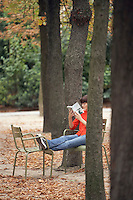 Woman reading book sitting on chairs in park