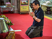 19 OCTOBER 2016 - BANGKOK, THAILAND:  Thais in mourning pray for the late Bhumibol Adulyadej, the King of Thailand, at Wat Pathum Wanaram in central Bangkok. The King died Oct. 13, 2016. He was 88. His death came after a period of failing health. Bhumibol Adulyadej was born in Cambridge, MA, on 5 December 1927. He was the ninth monarch of Thailand from the Chakri Dynasty and is also known as Rama IX. He became King on June 9, 1946 and served as King of Thailand for 70 years, 126 days. He was, at the time of his death, the world's longest-serving head of state and the longest-reigning monarch in Thai history.     PHOTO BY JACK KURTZ