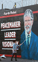 A young girl puts the finishing touches to a new mural of Gerry Adams which appeared on the Falls Road, west Belfast, Northern Ireland, on May 2, 2014. Police in Northern Ireland have been granted more time to question Irish republican leader Gerry Adams, head of the Sinn Fein political party who is being held over the murder of a woman in 1972. Northern Ireland police applied for more time to question republican leader Gerry Adams over a notorious IRA murder in 1972. Picture by Paul McErlane / i-Images