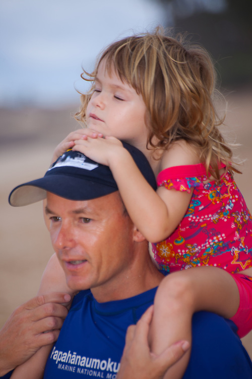 A little girl takes a nap on her daddy's shoulders on the beach in Hawaii