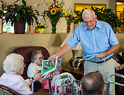 Deacon Harvey Quinette distributes parish bulletins to nursing home residents following a prayer service. (Sam Lucero photo)