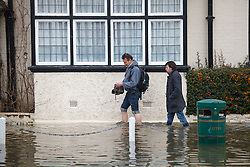 © Licensed to London News Pictures. 10/02/2014. Datchet, Berkshire, UK. Two men wading through flood water, one bare foot. Flooding in Datchet today, 10th February 2014 after the River Thames burst its banks. Photo credit : Rob Arnold/LNP
