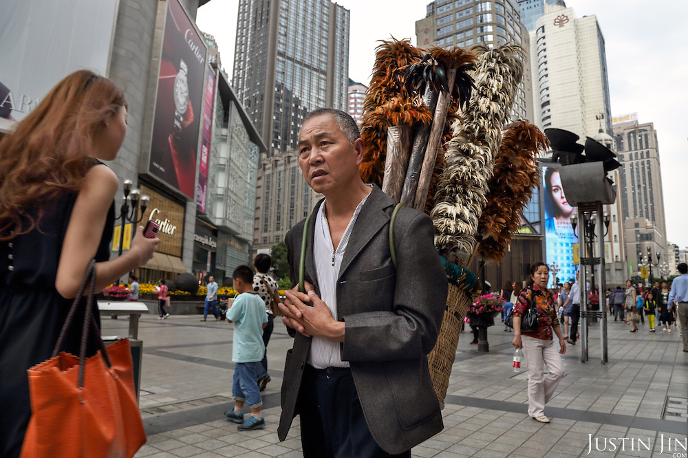 Liu Yong, a 59-year-old former farmer, ekes out a living in the city selling chicken-feather brushes in the centre of a Southwestern Chinese city.  <br /> <br /> He earns around 1,000 yuan a month selling these products, made of feathers he collects from chicken farms. <br /> <br /> His village was razed down several years ago by the government and has since lived in resettlement housing on the edge of the metropolis. <br /> <br /> China is pushing ahead with a dramatic, history-making plan to move 100 million rural residents into towns and cities between 2014 and 2020 &mdash; but without a clear idea of how to pay for the gargantuan undertaking or whether the farmers involved want to move.<br />
