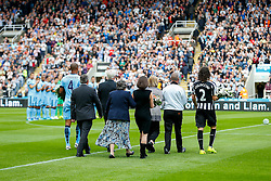 Vincent Kompany of Manchester City and Fabricio Coloccini of Newcastle United lead the families of the two Newcastle fans killed in the MH17 air disaster onto the pitch for a minutes silence. Liam Sweeney and John Alder were travelling to New Zealand to watch Newcastle play in a pre-season friendly tournament. - Photo mandatory by-line: Rogan Thomson/JMP - 07966 386802 17/08/2014 - SPORT - FOOTBALL - Newcastle, England - St James' Park - Newcastle United v Manchester City - Barclays Premier League.