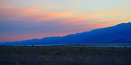 Tinted pink by the setting sun, smoke from a distant fire drifts over the mountains and into Death Valley.