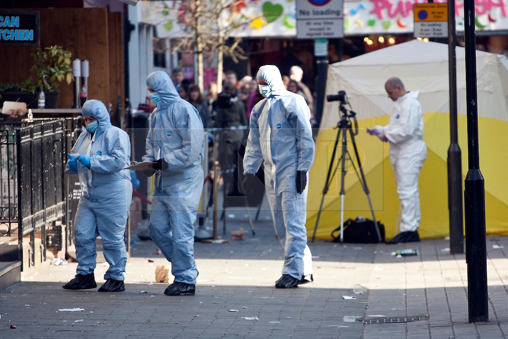© licensed to London News Pictures. London, UK 26/02/2012. Shoppers watch a forensic team investigating a crime scene on Inverness Street after a man was stabbed to death in Camden Town in the early hours of this morning 26 February 2012. Photo credit: Tolga Akmen/LNP