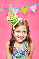 Tween blonde girl wearing a mint chocolate chip ice cream cone hat smiling towards camera against a pink seamless. Photographed at the Photoville Photo Booth September 20, 2015