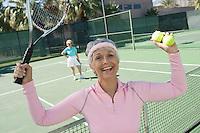 Senior woman celebrating on tennis court, portrait