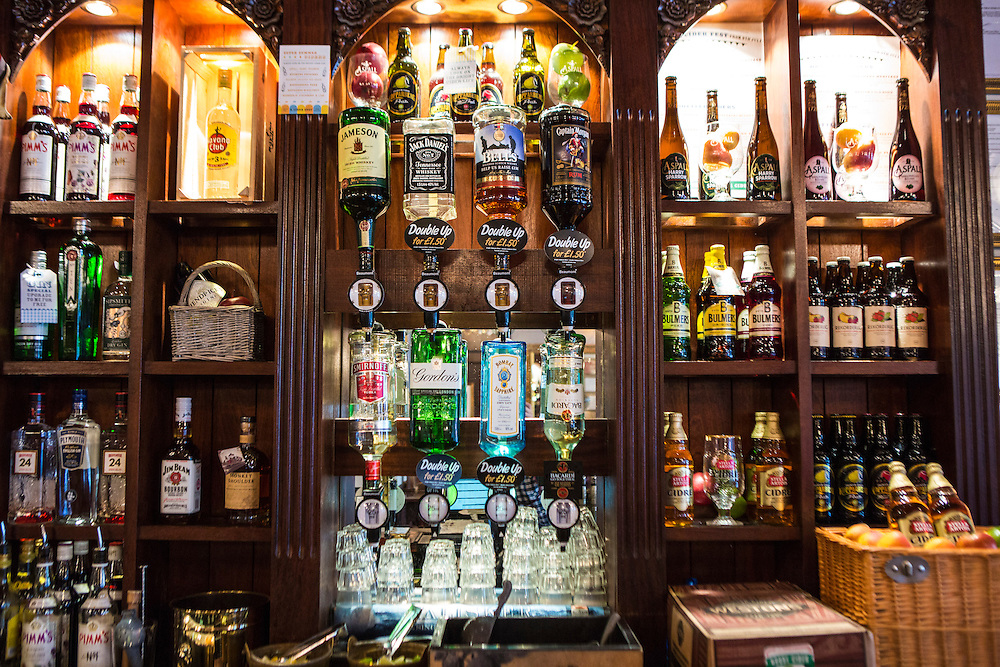 Behind the bar of a traditional English pub in London.  The pub is selling a variety of alcoholic drinks including beer, ale, cider, wine and hard liquor spirits. Pubs are a fundamental part of British culture and is often the focal point for a local community.  The excessive drinking culture in Britain is considered a public health issue.