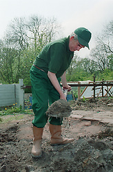 Man with learning disabilities at work on community allotment project digging soil with a spade,