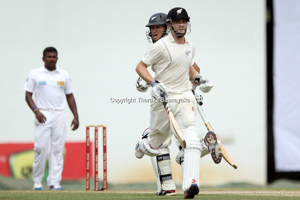 New Zealand cricket captain Ross Taylor (2R) and teammate Kane Williamson (R) run between the wickets as Sri Lankan spinner Rangana Herath looks on during the first day of the second and final Test match between Sri Lanka and New Zealand at the P. Sara Oval Cricket Stadium in Colombo on November 25, 2012. New Zealand captain Ross Taylor won the toss and elected to bat.