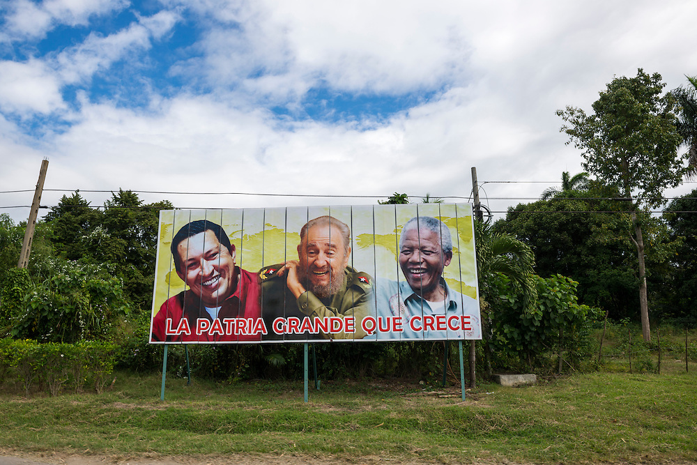 """A political billboard beside a highway near the city of Cienfuegos, Cuba, features smiling portraits of Hugo Chavez, Fidel Castro, and Nelson Mandela. The text can be translated as """"the great nation that grows""""."""