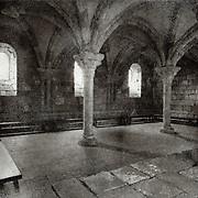 The interior of a medieval cloister showing details of the columns and pillars. This image was created using the Bromoil process.