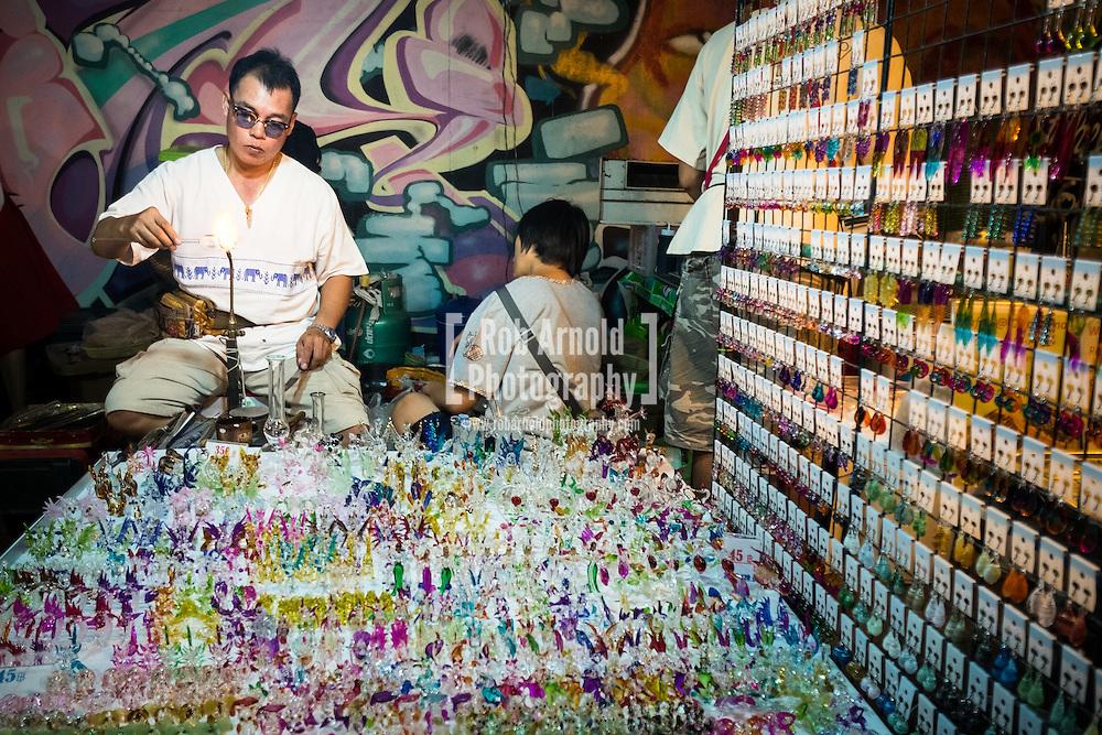 A man making glass souvenirs at the walking night market along Wualai Road in Chiang Mai, Thailand.