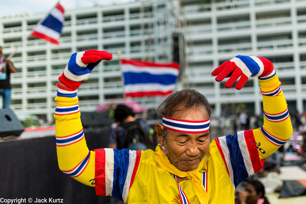26 NOVEMBER 2013 - BANGKOK, THAILAND:  A Thai anti-government protestor cheers an opposition speaker during a rally at the Ministry of Finance in Bangkok. Protestors opposed to the government of Thai Prime Minister Yingluck Shinawatra spread out through Bangkok this week. Protestors have taken over the Ministry of Finance, Ministry of Sports and Tourism, Ministry of the Interior and other smaller ministries. The protestors are demanding the Prime Minister resign, the Prime Minister said she will not step down. This is the worst political turmoil in Thailand since 2010 when 90 civilians were killed in an army crackdown against Red Shirt protestors. The Pheu Thai party, supported by the Red Shirts, won the 2011 election and now govern. The protestors demanding the Prime Minister step down are related to the Yellow Shirt protestors that closed airports in Thailand in 2008.    PHOTO BY JACK KURTZ