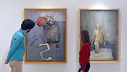 """© Licensed to London News Pictures. 15/11/2012. London, UK A man and woman look at two David Hockney Paintings from his time at the College. (L """"Composition - Thrust"""" and R """"Nude-Seated"""" both completed in 1962 Hockney was a Painting student 1959-62)  The Royal College of Art is celebrating its 175thanniversary with a major exhibition featuring more than 350 works of art and design by over 180 RCA graduates and staff, including Henry Moore, Barbara Hepworth, Tracey Emin, David Hockney, Peter Blake, Bridget Riley and Lucian Freud. The RCA is the world's oldest art and design university in continuous operation. Its first students comprised a small group of teenage boys; today it educates some 1,200 postgraduate students from 55 different countries.. Photo credit : Stephen Simpson/LNP"""