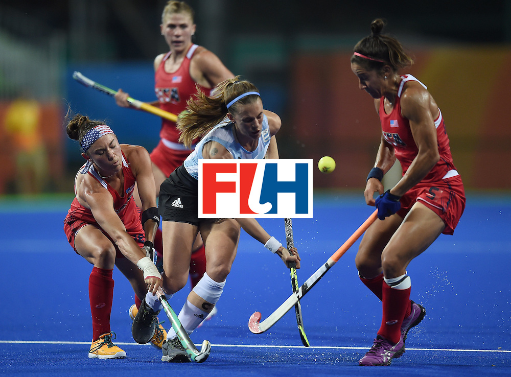 Argentina's Carla Rebecchi (C) tries to get past the USA's Melissa Gonzalez (R) and Michelle Kasold  during the women's field hockey Argentina vs USA match of the Rio 2016 Olympics Games at the Olympic Hockey Centre in Rio de Janeiro on August, 6 2016. / AFP / MANAN VATSYAYANA        (Photo credit should read MANAN VATSYAYANA/AFP/Getty Images)