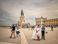 Futurs maries lors d'une prise de vue sur la Praça do Comercio.<br /> Cette place accueille le palais Royal pendant quatre siecles d'ou le nom sous lequel on la designe encore Terreiro do Paço (terrasse du palais). <br /> C'est en 1511 que Manuel Ier abandonne le Castelo de Sao Jorge pour s'installer sur la rive du Tage.<br /> La place a ete nommee Praça do Comercio pour indiquer sa nouvelle fonction dans l'economie de Lisbonne. <br />  La piece principale de l'ensemble etait la statue equestre du roi Joseph Ier, inauguree en 1775 au centre de la place. <br /> Cette statue de bronze, première statue monumentale dediee a un roi à Lisbonne, a été conçue par Joaquim Machado de Castro, un sculpteur portugais de l'epoque.
