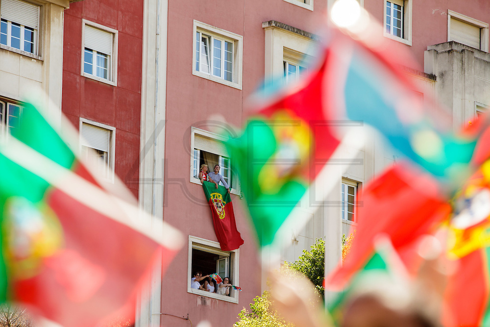 Portuguese supporters celebrating on their houses windows while   awaiting for the football team to arrive at Alameda Dom Afonso Henriques, in Lisbon. Portugal's national squad won the Euro Cup the day before, beating in the final France, the organizing country of the European Football Championship, in a match that ended 1-0 after extra-time.