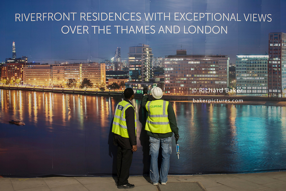 Workmen inspect their construction hoarding, a night time panorama of the Thames south bank, featuring riverside properties on the Thames - the future view of their new skyscraper.