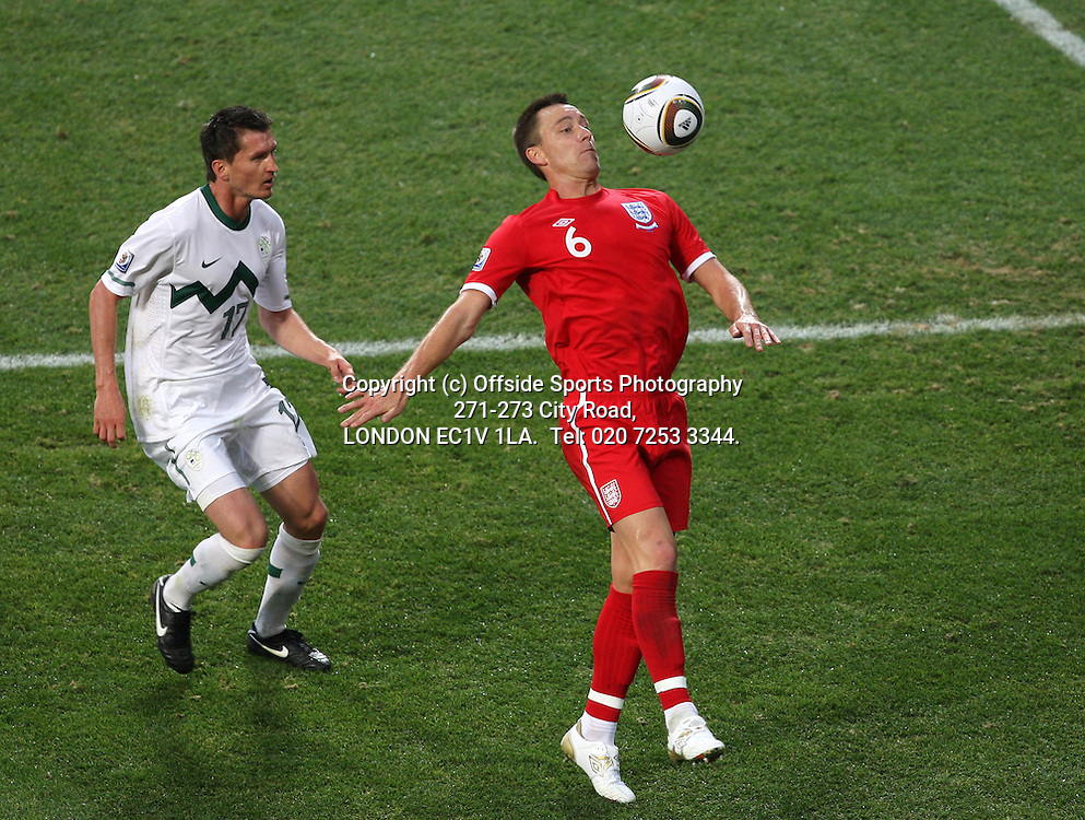 23/06/2010 World Cup. Slovenia v England.<br /> John Terry gets to the ball before Andraz Kirm.<br /> Photo: Mark Leech.