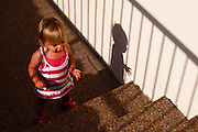 Young girl of two attempting to climb stairs