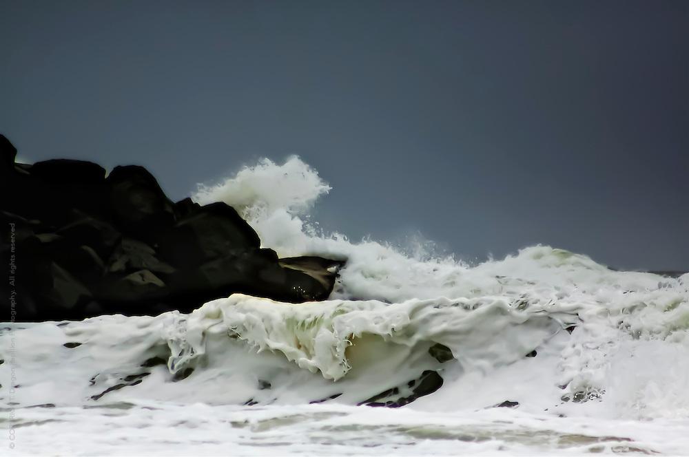 Seascape: foamy waves crashing against rocks shot on location at Brunswick Heads, NSW Australia