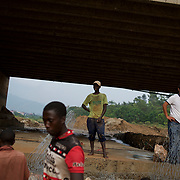 Local men are monitored by a Chinese engineer during the construction of a dam to prevent the erosion of the support pillars of a bridge in  central Bujumbura, Burundi.