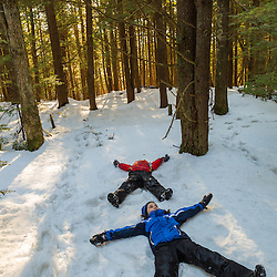 A brother and sister make snow angels on the Sweet Trail in the Society for the Protection of New Hampshire Forest's Dame Forest in Durham, New Hampshire. Winter.