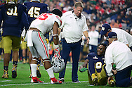 GLENDALE, AZ - JANUARY 01:  Running back Ezekiel Elliott #15 of the Ohio State Buckeyes (left) checks on an injured linebacker Jaylon Smith #9 of the Notre Dame Fighting Irish during the first quarter of the BattleFrog Fiesta Bowl at University of Phoenix Stadium on January 1, 2016 in Glendale, Arizona.  (Photo by Jennifer Stewart/Getty Images)