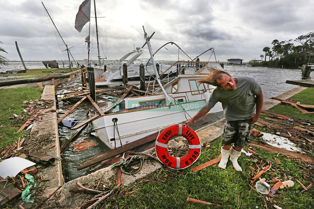 September 11, 2017 - Brevard County, Florida, U.S. - With tropical force gusts of winds still blowing PHILLIP ELZAS, 49, picks up the life preserver of the boat ''Easy Life,'' a trawler that sunk at Sundance Marine after Hurricane Irma blew through Brevard County.  Elzas stayed with his sailboat most of the night, but left when the weather got rough. Eight boats had sunk and many damaged. Debris from sunken boats and docks washed over the seawall onto the land as Hurricane Irma winds blew from the east. (Credit Image: © Red Huber/TNS via ZUMA Wire)