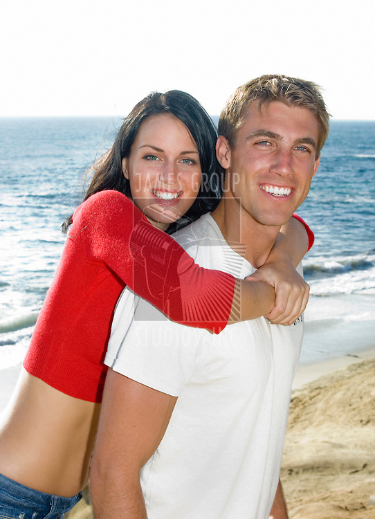 Attractive, young couple hugging on the coast