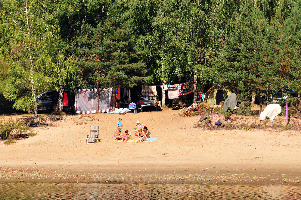 Families enjoy the last of summer in the late afternoon light along the banks of the Rybinsk Reservoir. Children will return to school September 1st. The Volga-Baltic Waterway, made up of natural lakes, rivers, reservoirs, and canals, runs from St. Petersburg to Moscow, Russia, a journey of 700 miles.