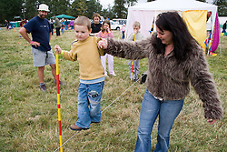 Woman helping young boy balance as he walks a tight rope at the Cropredy Festival  Fairport's Cropredy Convention  2005