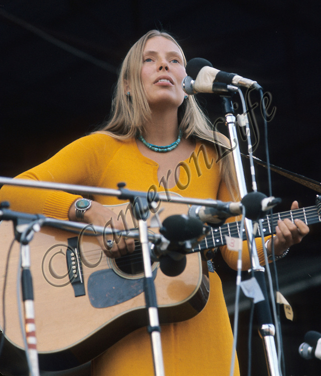 "Joni Mitchell .- .Born as Roberta Joan Anderson in 1943, Joni Mitchell was instrumental in penning such great songs as ""Both Sides Now"" (later made famous by Judy Collins) and her own hit ""Big Yellow Taxi"". The Isle of Wight festival wasn't her greatest moment however, as her stage appearance was initially repeatedly interrupted by protesters, finally reduced her to tears."