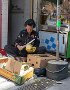 Woman cleaning fruit in Kat Hing Street, Tai O Fisging Village, Lantau Island, Hong Kong, China.